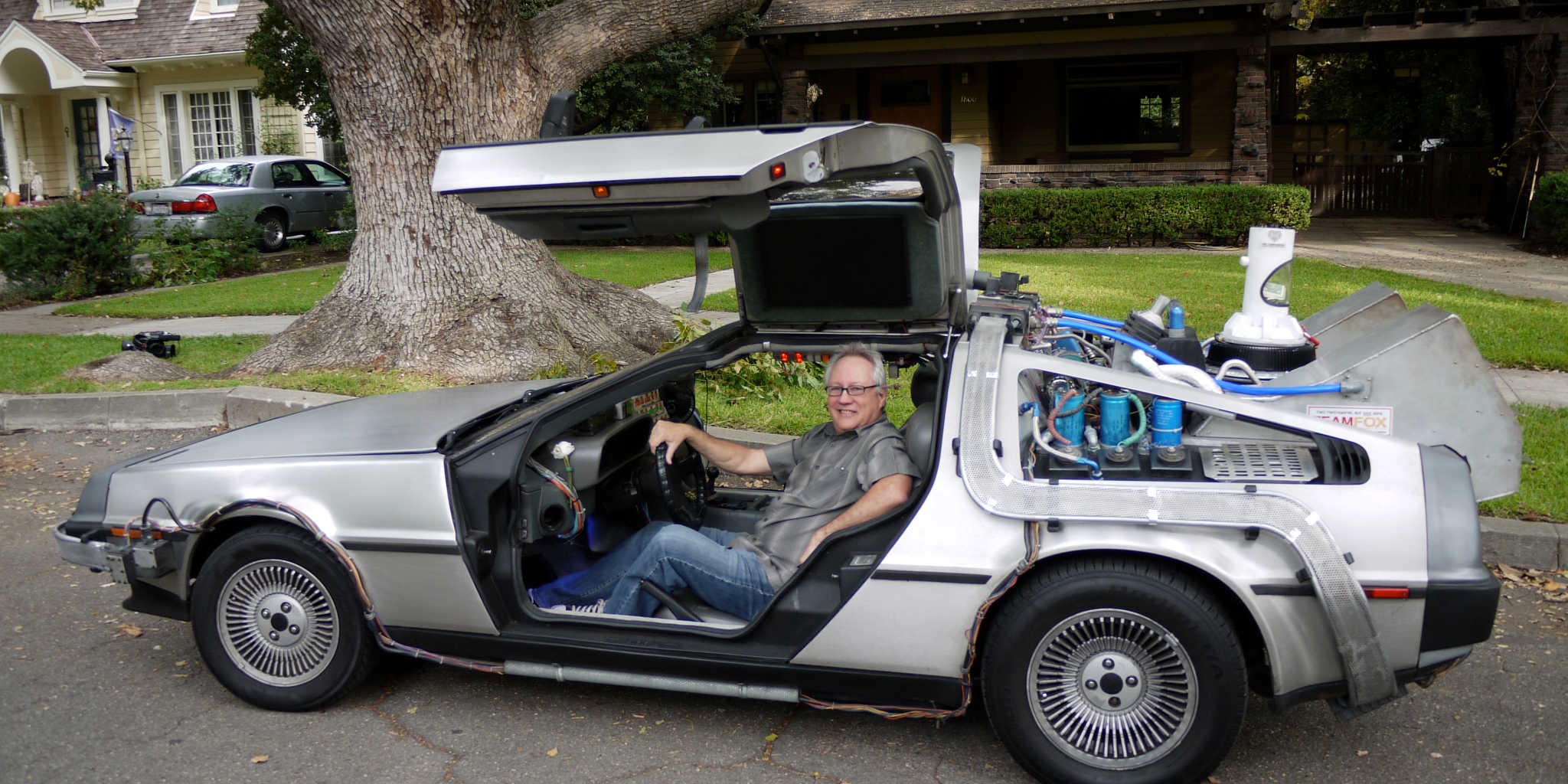 Filmmaker John McDonald siiting in front of the Peeping Tom tree in a replica of the Back to the Future DeLorean time machine